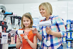 Mother and daughter chooses a hairdryer in shop Stock Photo