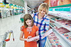 Mother and daughter chooses a meat in shop Royalty Free Stock Photo