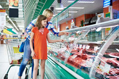 Mother and daughter chooses a meat in shop Stock Photography