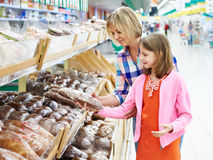 Mother and daughter choosing bread in supermarket Stock Photo