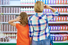 Mother and daughter choosing dairy products Stock Photos