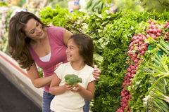 Mother and daughter choosing fresh produce stock photography