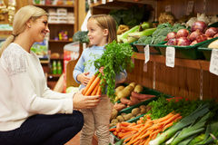 Mother And Daughter Choosing Fresh Vegetables In Farm Shop Royalty Free Stock Images