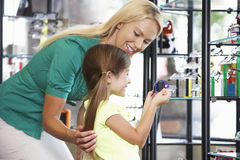 Mother And Daughter Choosing Glasses In Opticians Stock Photo
