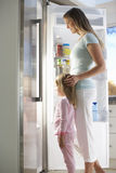 Mother And Daughter Choosing Snack From Fridge Stock Photography