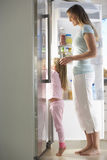 Mother And Daughter Choosing Snack From Fridge Royalty Free Stock Image