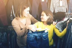 Mother and daughter choosing trendy jeans Royalty Free Stock Images