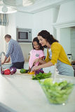 Mother and daughter chopping vegetables in kitchen Royalty Free Stock Images