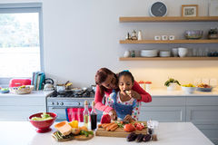 Mother and daughter chopping vegetables in kitchen Stock Image