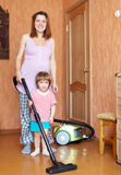 Mother and daughter chores with vacuum cleaner Royalty Free Stock Photo
