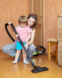 Mother and daughter chores with vacuum cleaner Stock Photos