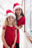 Mother and daughter in Christmas attire standing in jewelry shop Royalty Free Stock Photography