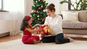 Mother and daughter with christmas gift at home stock footage