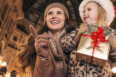 Mother and daughter with Christmas gift pointing on something Royalty Free Stock Photo