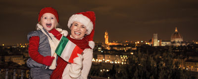 Mother and daughter in Christmas hats in Florence showing flag Stock Images