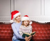 Mother and daughter in Christmas hats reading a book at home. Fairy tail concept Royalty Free Stock Images