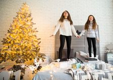 Mother and daughter in Christmas have fun. Mother and daughter in Christmas home at christmas tree giving each other presents Royalty Free Stock Image