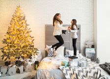 Mother and daughter in Christmas have fun. Mother and daughter in Christmas home at christmas tree giving each other presents Stock Photos