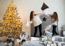 Mother and daughter in Christmas have fun. Mother and daughter in Christmas home at christmas tree giving each other presents Stock Images