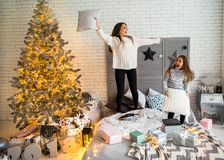 Mother and daughter in Christmas have fun. Mother and daughter in Christmas home at christmas tree giving each other presents Royalty Free Stock Photography