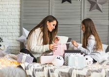 Mother and daughter in Christmas home at christmas tree giving e. Ach other presents Stock Photography