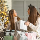 Mother and daughter at christmas home at christmas tree giving e Stock Photography