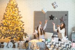 Mother and daughter in Christmas home at christmas tree giving e Royalty Free Stock Photos