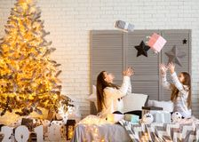Mother and daughter at christmas home at christmas tree giving e. Ach other presents.Young mother and her ittle daughters opening a magical Christmas gift by a Royalty Free Stock Photography