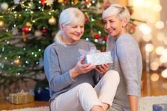 Mother and daughter by Christmas tree. Happy daughter giving mother Christmas gift royalty free stock photos