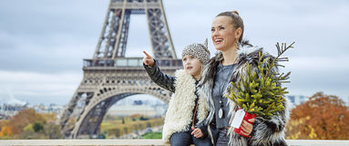 Mother and daughter with Christmas tree pointing on something. The Party Season in Paris. smiling trendy mother and daughter with Christmas tree in the front of Royalty Free Stock Photo