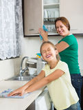 Mother with daughter cleaning at kitchen Royalty Free Stock Images