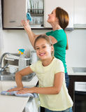 Mother with daughter cleaning at kitchen Stock Image