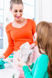 Mother and daughter cleaning window in apartment Royalty Free Stock Image