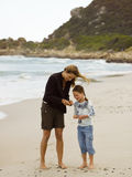 Mother and daughter collecting sea shells on the beach. Royalty Free Stock Photography