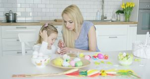 Mother and daughter coloring eggs stock footage