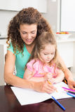 Mother and daughter colouring together at the table Stock Photos
