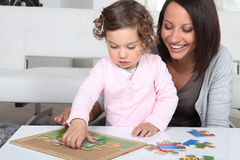 Mother and daughter completing jigsaw Royalty Free Stock Photography