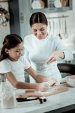 Concentrated child preparing dinner with mom in the kitchen royalty free stock photos