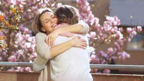 Mother and daughter congratulate each other on Mother`s Day. Daughter hugs an elderly mother against the background of a