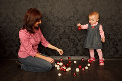Mother and daughter consider Christmas decorations Royalty Free Stock Images