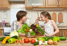Mother and daughter cook and taste soup from vegetables. Home kitchen interior. Parent and child, woman and girl. Healthy food con. Mother and daughter cook and Stock Images