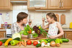 Mother and daughter cook and taste soup from vegetables. Home kitchen interior. Parent and child, woman and girl. Healthy food con Royalty Free Stock Image