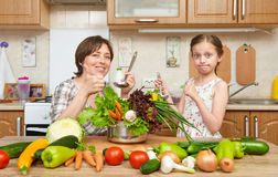Mother and daughter cook and taste soup from vegetables. Home kitchen interior. Parent and child, woman and girl. Healthy food con Stock Photos