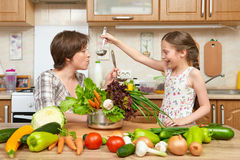Mother and daughter cook and taste soup from vegetables. Home kitchen interior. Parent and child, woman and girl. Healthy food con Stock Photo