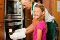 Mother and daughter cooking stock photos