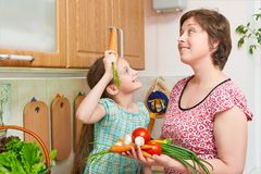 Mother and daughter cooking. Basket of vegetables and fresh fruits in kitchen interior. Parent and child. Healthy food concept Stock Image