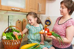 Mother and daughter cooking. Basket of vegetables and fresh fruits in kitchen interior. Parent and child. Healthy food concept Royalty Free Stock Photo