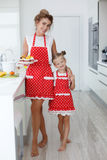 Mother and daughter cooking cupcakes on the festive table Stock Image