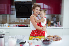 Mother and daughter cooking cupcakes on the festive table Stock Photography