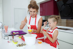 Mother and daughter cooking cupcakes on the festive table Royalty Free Stock Image